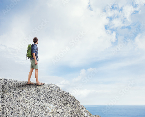 Young traveler standing on a rock