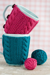 Two blue cups in blue and pink sweater with ball of yarn