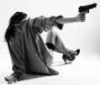 Undressed girl sits back and aims with handgun