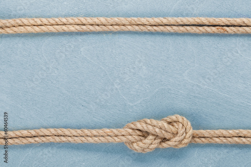 Leinwanddruck Bild Ship rope knot on wooden texture background