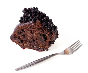 Piece of cake with chocolate glaze and blueberries
