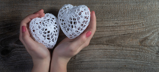 Woman hands holding white lace hearts on old wood background.