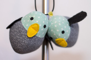 Two handmade textile birds hanging