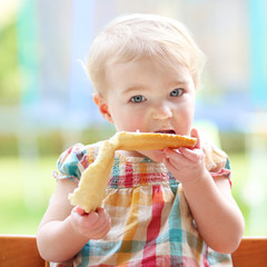 Cute blonde toddler girl eating tasty bread with butter