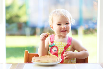 Happy little toddler girl eating delicious pancakes