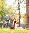 Beautiful female sitting on a grass with her dog in a park