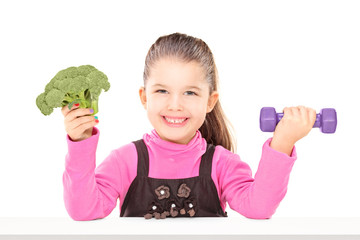 Adorable little girl holding broccoli and a dumbbell, seated at