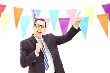 Young businessman with birthday hat singing at a party