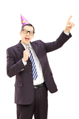 Young businessman with party hat singing on microphone