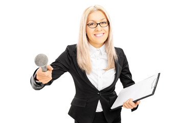 Young female interviewer holding clipboard and microphone