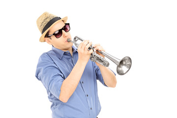 Young male musician with sunglasses playing trumpet