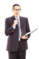 Young male presenter holding microphone and clipboard