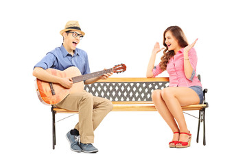Young man playing acoustic guitar to his excited girlfriend seat