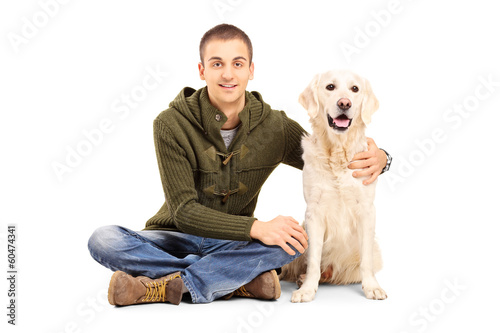 Young man in casual clothes sitting on floor with his Labrador r