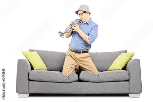 Young man sitting on sofa and blowing on trumpet