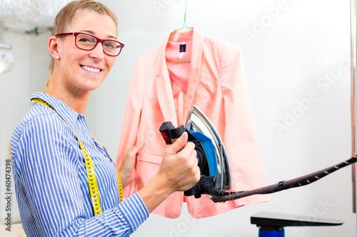 Textilreinigerin  einer Reinigung bügelt Jackett
