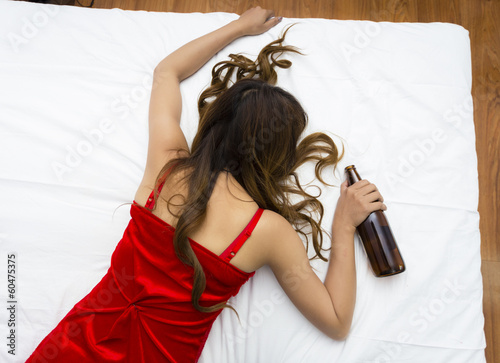 Drunk young woman sleeping on bed with bottle of vine in hand
