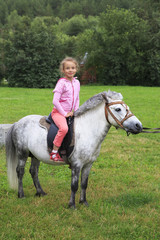 Beautiful girl riding a pony.