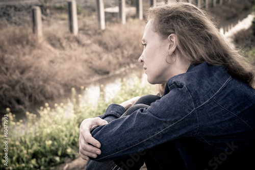 one sad woman sitting  near a river