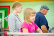 Adorable girl at shopping cart and mother stay in queue at cash