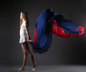 Graceful little athlete posing with colorful cloth