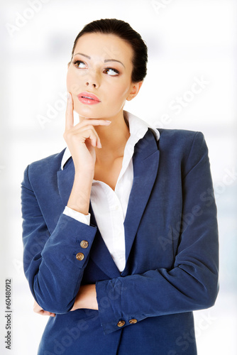 Young thoughtful businesswoman looking on side