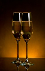 a pair of champagne flutes on dark golden light background
