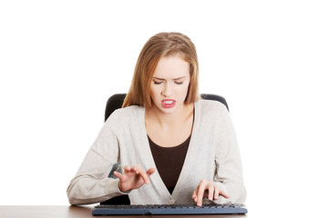 Beautiful casual woman writing on keyboard with anger.
