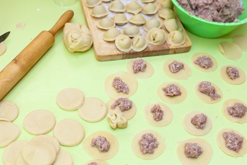 Rolling pin, dough and raw pelmeni