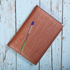 in leather-bound notebook on a wooden background