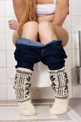 Young caucasian woman is sitting on the toilet. urinary bladder