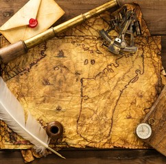 Different tools  on vintage map over wooden background