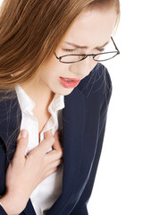 Beautiful business woman touching her chest, feeling unwell.
