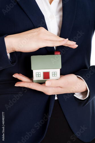 Close up on house modal in business woman's hands.