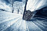 Car tires on winter road poster