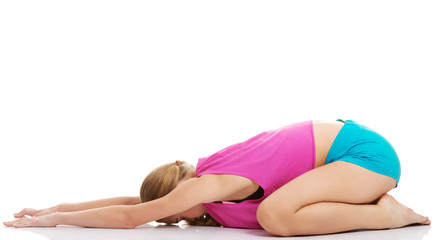 Young caucasian woman is exercising, stretching herself.