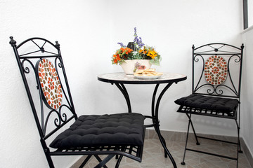 Chairs and a table with artificial flowers and pastry plate.