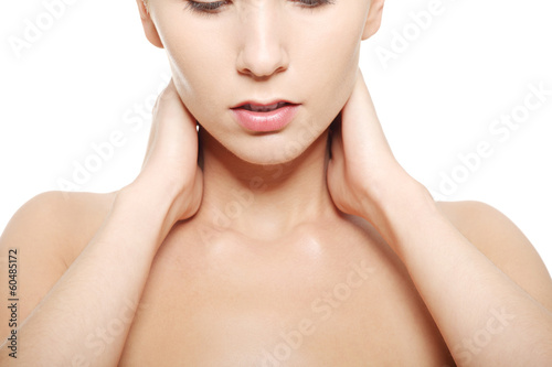 Naked woman touching her neck, head and shoulders close up.