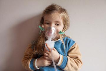 Little girl holding inhalation mask
