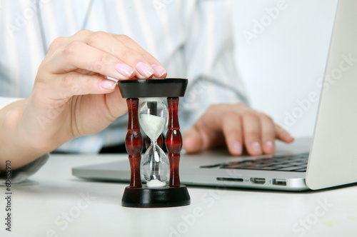 Young business woman with hourglass - time concept.
