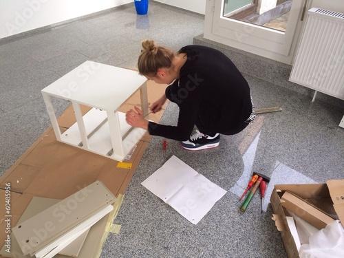 Junge Frau beim Möbel zusammenbauen