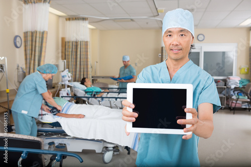 Male Nurse Showing Digital Tablet In Hospital Ward