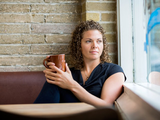 Woman Looking Through Window At Cafeteria