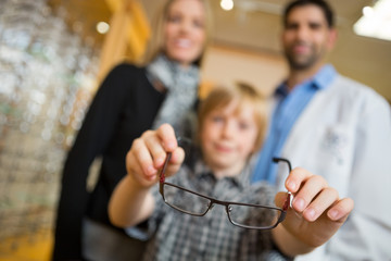 Boy Showing Glasses With Mother And Optician In Store