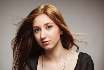 Portrait of beautiful girl with fluttering hairon a grey