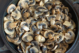 Many sliced fried mushrooms in old black pan closeup