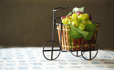 Violet and green Grapes in cute small bicycle