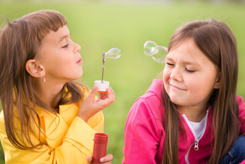 Portrait of cute girl blowing soap bubbles