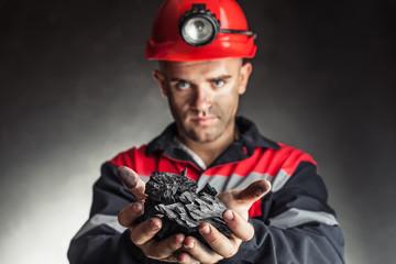 Coal miner holding lump of coal