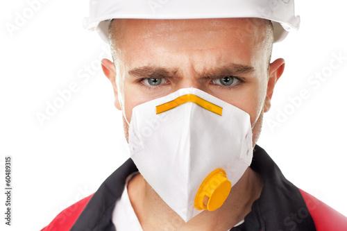 Serious worker wearing respirator - 60489315